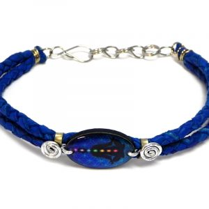 Handmade braided dyed leather bracelet with silver metal wire and oval-shaped acrylic New Age themed chakra flower of life graphic design centerpiece in royal blue, black, and rainbow color combination.