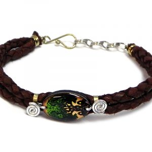 Handmade braided dyed leather bracelet with silver metal wire and oval-shaped acrylic New Age themed tree of life graphic design centerpiece in brown, tan, and green color combination.