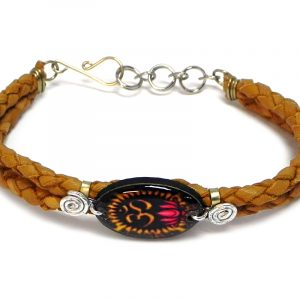 Handmade braided dyed leather bracelet with silver metal wire and oval-shaped acrylic New Age themed om sign lotus flower graphic design centerpiece in tan, brown, gold, black, and hot pink color combination.