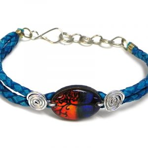 Handmade braided dyed leather bracelet with silver metal wire and oval-shaped acrylic New Age themed tree of life graphic design centerpiece in turquoise blue, blue, orange, and black color combination.