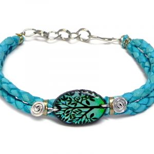 Handmade braided dyed leather bracelet with silver metal wire and oval-shaped acrylic New Age themed tree of life graphic design centerpiece in turquoise blue, mint green, and black color combination.