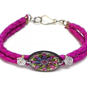 Handmade braided dyed leather bracelet with silver metal wire and oval-shaped acrylic New Age themed floral mandala graphic design centerpiece in magenta pink and multicolored color combination.