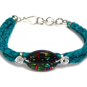 Handmade braided dyed leather bracelet with silver metal wire and oval-shaped acrylic New Age themed geometric hamsa hand graphic design centerpiece in teal green and multicolored color combination.