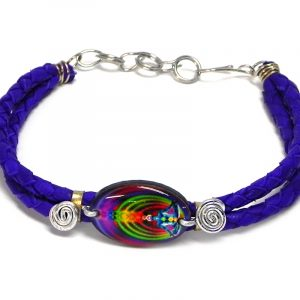 Handmade braided dyed leather bracelet with silver metal wire and oval-shaped acrylic New Age themed chakra graphic design centerpiece in indigo purple and rainbow color combination.