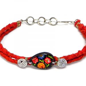 Handmade braided dyed leather bracelet with silver metal wire and teardrop-shaped acrylic vintage themed floral pattern graphic design centerpiece in red, black, and multicolored color combination.
