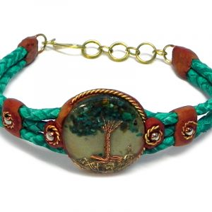 Handmade braided dyed leather bracelet with brown resin, gold-colored metal, and round-shaped clear acrylic resin, copper wire, and crushed chip stone inlay tree of life centerpiece in teal green color.