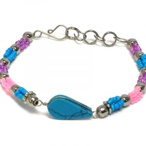 Handmade multicolored seed bead and silver metal bead rope-like bracelet with teardrop-cut turquoise howlite gemstone crystal cabochon centerpiece in turquoise blue, pink, and purple lavender color combination.