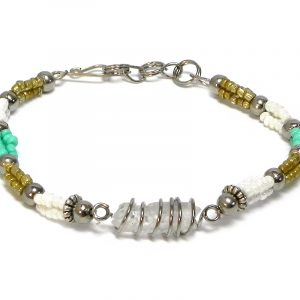 Handmade multicolored seed bead and silver metal bead rope-like bracelet with wire wrapped clear quartz crystal centerpiece in white, gold, and mint green color combination.