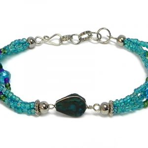 Handmade seed bead and crystal bead multi strand bracelet with teardrop-cut teal chrysocolla gemstone crystal cabochon centerpiece in turquoise blue, green, and purple color combination.