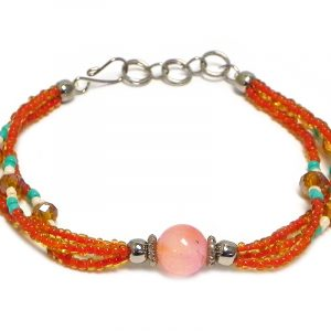 Handmade seed bead and crystal bead multi strand bracelet with tumbled orange agate gemstone crystal ball bead centerpiece in orange, mint green, and pearl white color combination.