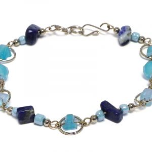 Handmade chip stone, seed bead, and crystal bead silver metal chain link loop bracelet in blue sodalite, light blue, and turquoise color combination.
