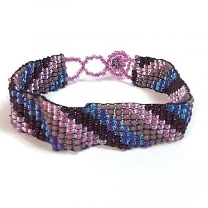 Handmade Czech glass seed bead thin strap bracelet with slanted striped pattern design in purple, burgundy, and pink color combination.