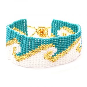 Handmade Czech glass seed bead wide strap bracelet with wave pattern design in turquoise blue, white, and gold color combination.
