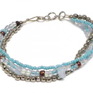 Handmade large seed bead and silver metal bead thick multi strand bracelet with chip stones in light blue and iridescent white color combination.