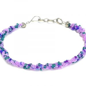 Handmade thin braided seed bead bracelet in lavender, purple, and teal green color combination.