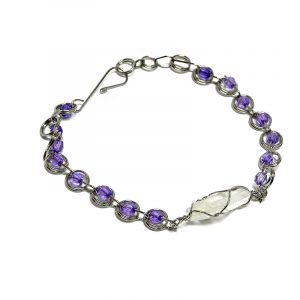 Handmade seed bead silver metal chain link loop bracelet with wire wrapped clear quartz crystal centerpiece in purple color.
