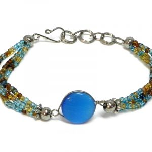Handmade multicolored seed bead multi strand bracelet with round-shaped cat's eye glass bead centerpiece in light blue, turquoise, gold, and brown color combination.