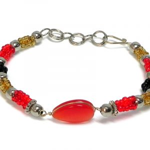 Handmade multicolored seed bead and silver metal bead rope-like bracelet with teardrop-shaped cat's eye glass bead centerpiece in red, gold, and black color combination.