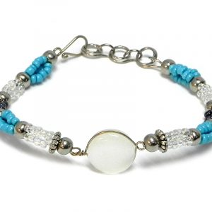 Handmade multicolored seed bead and silver metal bead rope-like bracelet with round-shaped cat's eye glass bead centerpiece in white, clear, turquoise blue, and dark gray charcoal color combination.