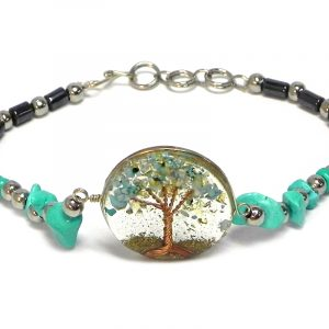 Handmade hematite, chip stone, and silver metal seed bead bracelet with round-shaped clear acrylic resin, copper wire, and crushed chip stone inlay tree of life centerpiece in mint turquoise color.