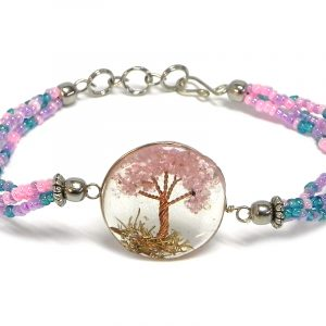 Handmade multicolored seed bead multi strand bracelet with round-shaped clear acrylic resin, copper wire, and crushed chip stone inlay tree of life centerpiece in pink, turquoise blue, and purple lavender color combination.