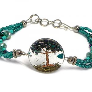 Handmade crystal bead and seed bead multi strand bracelet with round-shaped clear acrylic resin, copper wire, and crushed chip stone inlay tree of life centerpiece in teal green, turquoise mint, and iridescent navy blue color combination.