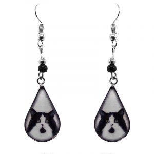 Teardrop-shaped Tuxedo cat face graphic acrylic dangle earrings with silver metal setting and beaded metal hooks in white and black color combination.