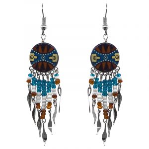 Handmade round-shaped ceramic earrings with handpainted tribal pattern design and long seed bead and alpaca silver metal dangles in brown, turquoise, white, black, and light yellow color combination.
