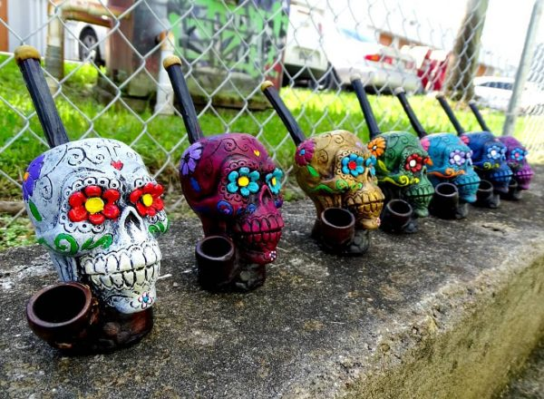 Handcrafted medium-sized tobacco smoking hand pipe of a Day of the Dead sugar skull with multicolored floral designs.