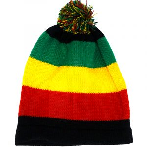 Handmade knit beanie hat with horizontal striped pattern and pom pom puff ball in Rasta colors.