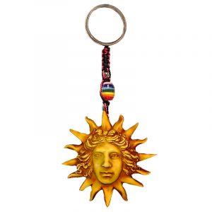 Handmade durepox resin figurine keychain of a golden yellow face with sun rays.