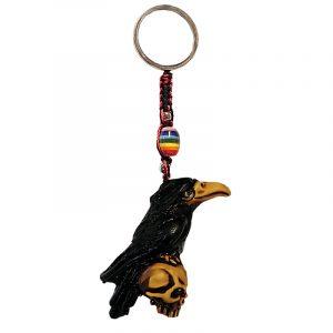 Handmade durepox resin figurine keychain of a black raven bird perched on a skull.