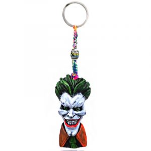 Handmade durepox resin figurine keychain of an evil clown character with a big head, creepy smile, green hair, and suit.