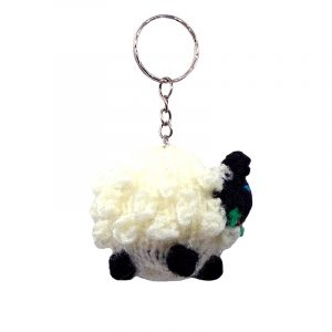 Handmade wool finger puppet keychain of a sheep with silver metal key ring in white and black color combination.