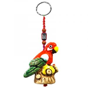 Handmade parrot animal keychain with handpainted ceramic, macramé string, a large bead, and metal keyring in red, white, green, and yellow color combination.