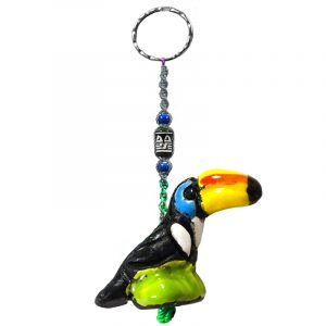 Handmade toucan animal keychain with handpainted ceramic, macramé string, a large bead, and metal keyring in black, white, turquoise blue, yellow, and green color combination.