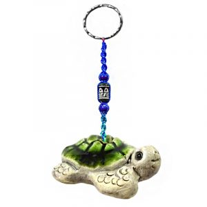 Handmade sea turtle animal keychain with handpainted ceramic, macramé string, a large bead, and metal keyring in green and beige color combination.