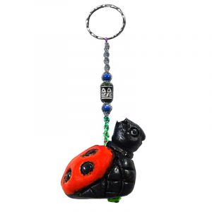 Handmade ladybug animal keychain with handpainted ceramic, macramé string, a large bead, and metal keyring in red and black color combination.