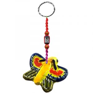 Handmade butterfly animal keychain with handpainted ceramic, macramé string, a large bead, and metal keyring in yellow, orange, and blue color combination.