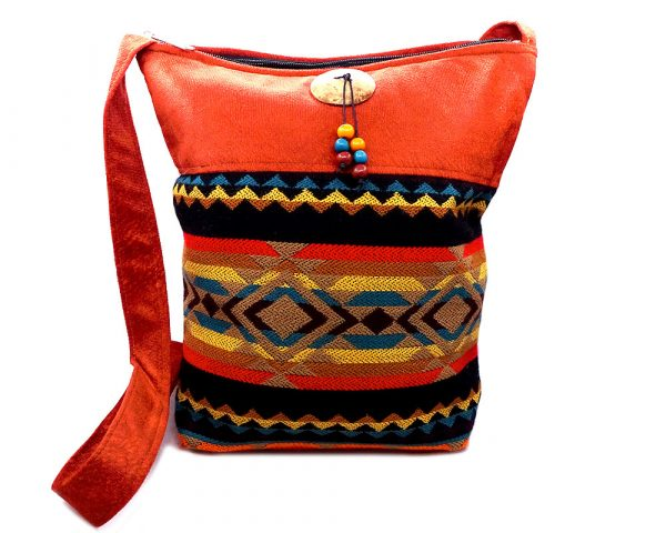 Handmade large cushioned square-shaped crossbody purse bag with Aztec inspired tribal print pattern material, vegan suede, and coconut button and beads in dark orange, tan, brown, black, golden yellow, and dark blue color combination.