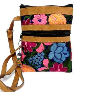 Medium-sized slim rectangle-shaped crossbody purse bag with multicolored embroidered floral designs, brown vegan leather suede, worry doll keychain, and indigo fabric.