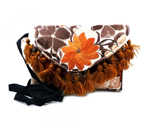Handmade slim envelope purse bag with floral embroidered cotton material, pom pom fringe, magnetic snap closure, and a crossbody strap in white and brown color combination.