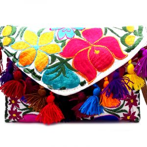 Handmade slim envelope purse bag with floral embroidered cotton material, pom pom fringe, magnetic snap closure, and a wristlet strap in white and multicolored color combination.