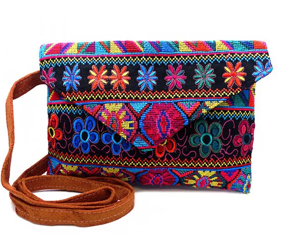 Handmade slim envelope purse bag with floral tribal huipil embroidered cotton material, magnetic snap closure, and a crossbody strap in black, orange, and multicolored color combination.