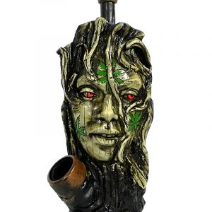 Handcrafted medium-sized tobacco smoking hand pipe of a tree woman face with red eyes and multiple green hemp leaves.