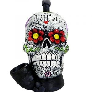 Handcrafted medium-sized tobacco smoking hand pipe of a white Day of the Dead sugar skull with multicolored floral designs.