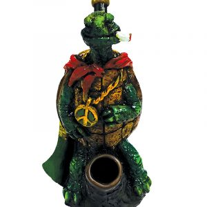 Handcrafted medium-sized tobacco smoking hand pipe of a smoking superhero turtle with a cape and peace sign chain in Rasta colors.