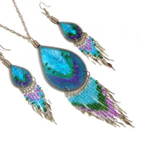 Handmade beaded teardrop-shaped silk thread necklace and matching earrings with long seed bead and alpaca silver metal dangles in turquoise blue, green, and purple color combination.