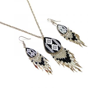 Handmade teardrop-shaped ceramic chain necklace and matching earrings with handpainted tribal pattern design and long seed bead and alpaca silver metal dangles in white, black, and clear color combination.
