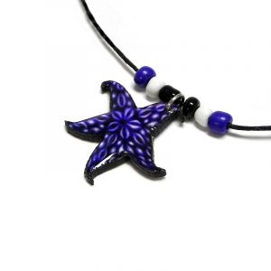 Handmade tropical starfish acrylic pendant with seed beads on black necklace in indigo, white, and black color combination.